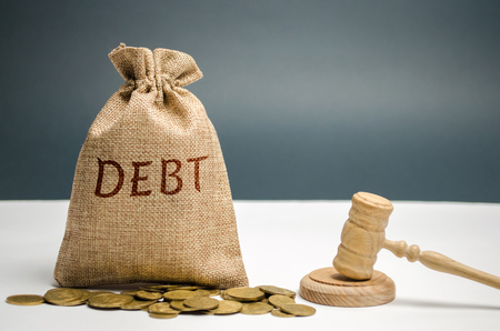 A bag of money and the word Debt and the hammer of the judge. Payment of taxes and of debt to the state. Concept of financial crisis and problems. Risk management. Debt exemption. Credit and loan Imagens - 113940228