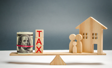Wooden house and family with the inscription Tax on the scales. Taxes on real estate, payment. Penalty, arrears. Register of taxpayers for property. Law-abiding, evasion of payment. Court law