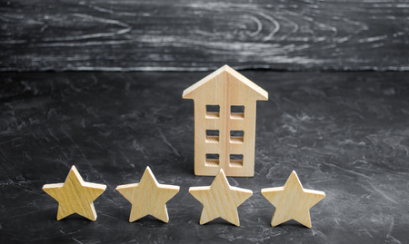 Wooden house and four stars on a gray background. Rating of houses and private property. Buying and selling, renting apartments. The level of the restaurant and hotels. Rating four stars. 版權商用圖片