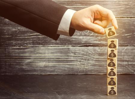 L'uomo d'affari mette un blocco con un'immagine di dollari. L'accumulazione di capitale e il business di successo. Aumento del budget e dei profitti nel team. Aumentare il fondo di investimento. Risparmiare soldi. Boom economico Archivio Fotografico