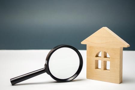 Holzhaus und Lupe. Immobilienbewertung. Standortwahl für den Bau. Haussuchkonzept. Suche nach Wohnungen und Wohnungen. Immobilienkonzept. Hausbewertung Standard-Bild