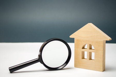 Wooden house and magnifying glass. Property valuation. Choice of location for the construction. House searching concept. Search for housing and apartments. Real estate concept. Home appraisal 免版税图像