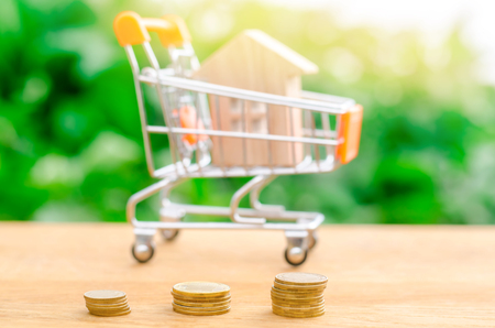 Stacks of coins and a wooden house. The concept of saving money for buying a home. Buy an apartment, real estate. Payment of rent for the apartment. Property tax repayment. Soft Focus on the coins.