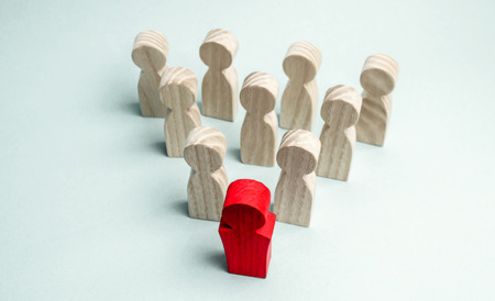 Wooden figures of people. The boss of the business team indicates the direction of movement to the goal. The crowd is following the leader. The concept of leadership and team management. Teamwork. Stok Fotoğraf