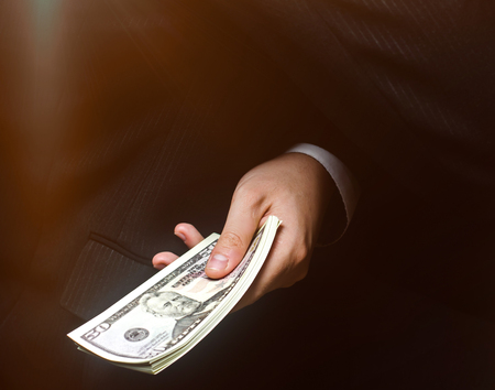 The concept of corruption and bribery, law and money. Dark business. Businessman receives money - Bribe in the form of dollar bills. Hand receiving money from businessman. Selective focus