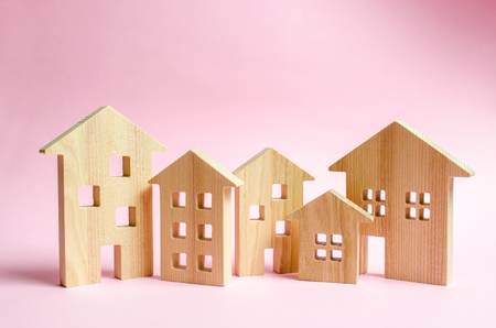 A lot of wooden houses on a pink background. The concept of the city or town. Investing in real estate, buying a house. Management and business management, market coverage. Construction of buildings. Stok Fotoğraf