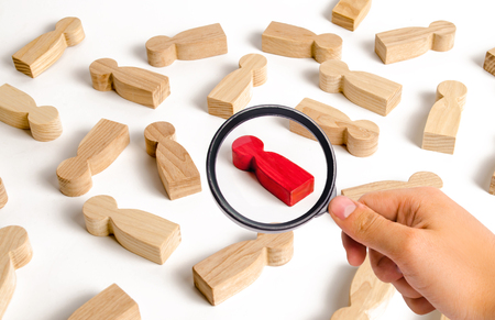 Magnifying glass is looking at the red human figure among many other people. Employee search concept, recruitment and personnel management. Zero infected. A talented worker, the best in his craft. Stockfoto