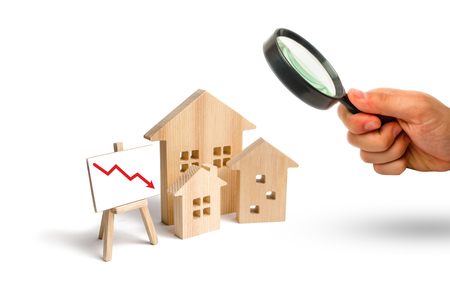 Magnifying glass is looking at the figures Wooden houses and red arrow down. The concept of falling prices and demand for real estate, crisis and recession, fall in the rate of construction quality