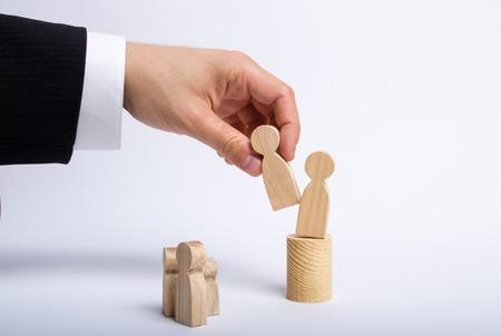 Die Hand eines Mannes eines Geschäftsmannes in einem Business-Anzug hält eine Holzfigur eines Mannes in der Hand und bewegt eine andere Figur von seinem Posten. Das Konzept der Entlassung eines Mitarbeiters, der Ersatz von Mitarbeitern