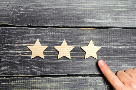 The hand points to the third star on a dark background. Rating, level of quality. Universal recognition, success and high efficiency. Evaluation of the hotel or restaurant. Application in the market.