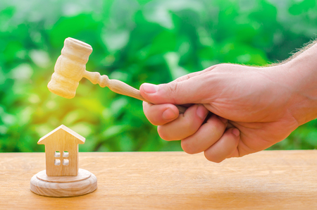 The judges hand is holding a hammer next to the wooden house. trial of real estate. Elimination and alienation of bankruptcy, confiscation and nationalization. Decision of property disputes.