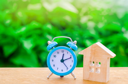 Wooden house and blue alarm clock on a green background. The concept of rent housing monthly and hourly. Temporary affordable accommodation, hotels and hostels. A loan to buy a house.