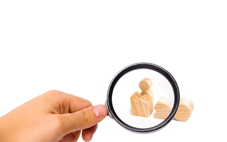 Magnifying glass is looking at a small figure of a man looks out of the remains of a large figure. The concept of revival and liberation, a way out of the comfort zone. Start a new life Stock Photo