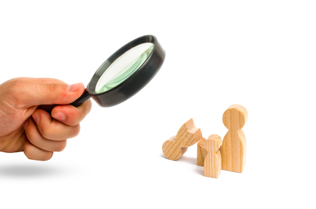 Magnifying glass is looking at a broken wooden figure of a man with a partner and a child. Strife in the family. One parent is broken, addicted to drugs or alcohol, gaming addiction. Single, divorce.