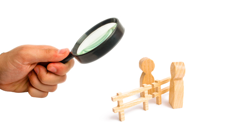 Magnifying glass is looking at the wooden fence divides the two persons discussing the case. Termination and breakdown of relations, breaking ties. Contract break, conflict of interests.