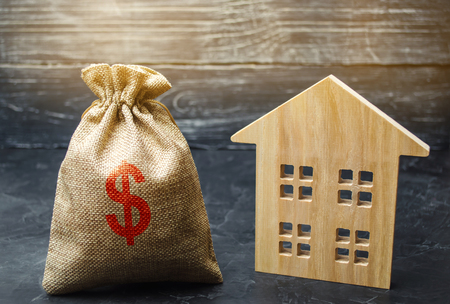 A bag with money and wooden house. Selling a house. Apartment purchase. Real estate market. Rental housing for rent. Home prices. Mortgage interest. Purchase demand. Property valuation. Insurance 免版税图像