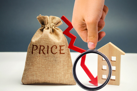 Money bag with word price, down arrow and wooden house. The concept of falling property prices. Lower housing prices. Low rent. The decline in the value of the property. Low utility prices 写真素材