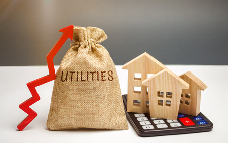 Money bag with the word Utilities and an up arrow and houses on a calculator. The concept of raising prices for the use of utilities. Payment of bills. Rising prices for water, electricity and heating Stok Fotoğraf