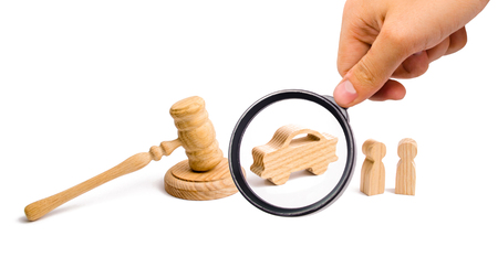 Magnifying glass is looking at the Wooden figurine of a car with people in a hammer of the judge on a white background. Minimalism. Purchase and sale of the car. The trial Recognition of ownership. Stockfoto