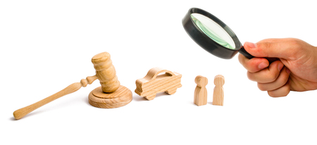 Magnifying glass is looking at the Wooden figurine of a car with people in a hammer of the judge on a white background. Minimalism. The trial, confiscation of the machine. Recognition of ownership.