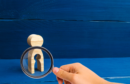 The concept of the loss of child, abortion of pregnancy, miscarriage. Infertility in women. Magnifying glass is looking at the wooden figure of a woman with a void inside in the shape of a child