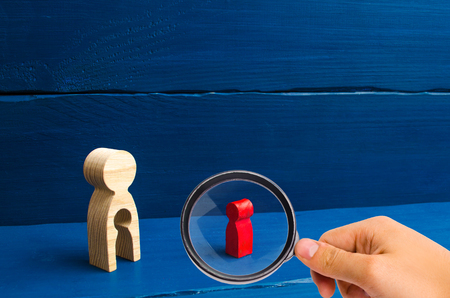Magnifying glass is looking at the wooden figure of a woman with a void in the form of a child inside the body stands and looks at the child. The concept of infertility in women. reunification.