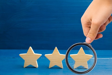 Magnifying glass is looking at the rating of the hotel, restaurant, mobile application. Three stars on a blue background. The concept of rating and evaluation. Quality service, buyer choice. Success Banque d'images - 116139757