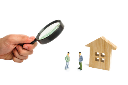 Two men are standing near a wooden house on a white background. The concept of discussing the terms of the transaction and the details of the contract. Buying and selling a house. In search