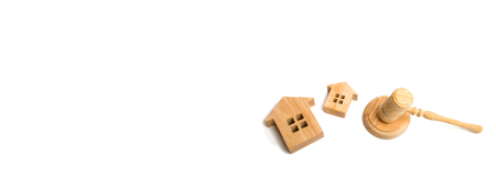 Two wooden houses and a hammer of the judge on a white background. concept of court cases on property and real estate. Confiscation and nationalization, confirmation of tenure rights. Banner copyspace