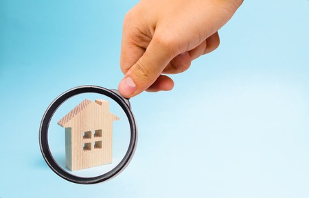 Magnifying glass is looking at the Wooden house on a blue background. The concept of affordable housing and mortgages to buy a house. Buying and selling apartments and property, real estate. Standard-Bild