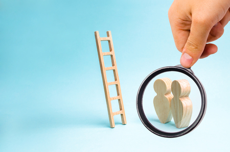 Magnifying glass is looking at the People stand and look at the stairs. Ladder to nowhere, career ladder. Promotion at work, business, self-development and leadership skills, social rating system Stock Photo