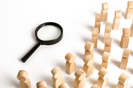 Wooden figures of people look at the magnifying glass. Search for answers to questions, searches for home or work. Problem solving and tasks, self-organization of people. Frequently asked Questions