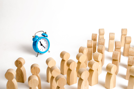 A crowd of people looks at the blue clock. Attention people are chained to the clock. Waiting for events over time. Relocation hours. Work day and hourly pay. Limited offer or time limit.