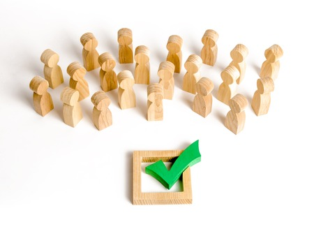 A crowd of people looks at a green check mark. Voting and election concept. Referendum, revolution. Forcible overthrow. Making the right decision, majority agreement. Peace and order, legitimization. Stock Photo