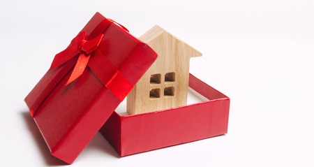 Wooden miniature house in a gift box. Housing as a gift. Win an apartment in the lottery. To inherit property. Holiday discounts. Buying an apartment at a low price. Sale of real estate. Present