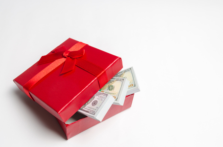 Dollars in a red gift box on a white background. Search for a gift for the holiday. Gift Certificate. The best gift is money. Cost of presents. Valentine's Day. Birthday. Saving money. Accumulation Stock Photo