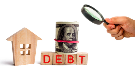 Wooden house and the inscription Debt and dolars. Real estate, home savings, loans market concept. Payment of real estate tax. Mortgage. Risks of buying a house. Foreclosure
