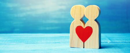 Ein verliebtes Paar und ein Herz zwischen ihnen. Das Konzept der Liebe und Sympathie zwischen zwei Menschen. Begegnung mit der Liebe allen Lebens. Menschliches Glück. Partnersuche. Liebeserklärung. Valentinstag. Minimalismus Standard-Bild