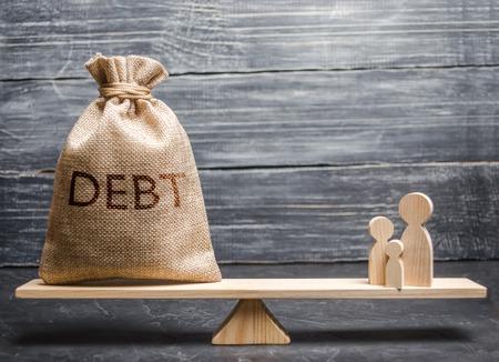 Una borsa con l'iscrizione debito e figure familiari sulla bilancia. Il concetto di onere loun sulle famiglie. Analfabetismo finanziario, fossa del debito e analfabetismo finanziario. Popolazione vulnerabile. Archivio Fotografico