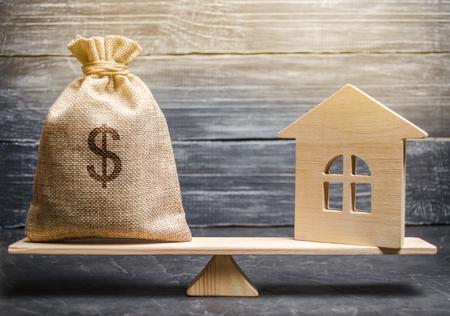 Ein Geldsack und ein Holzhaus auf der Waage. Das Konzept des Immobilienkaufs. Verkauf von Immobilien. Zahlung der Hypothek. Befreiung von Steuern. Steuerrückerstattung. Alt- / Erbschaftsteuerkonzept
