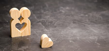 A miniature couple in love and a heart near them. The concept of family problems and loss of feelings for your loved one. Consultation family psychologist. Rupture / divorce. Selective focus Stock Photo