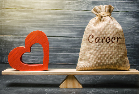Bag with money with the word Career and red wooden heart on the scales. Money versus love concept. Passion versus profit. Family or career choice. Family psychology. Mind vs. Passion