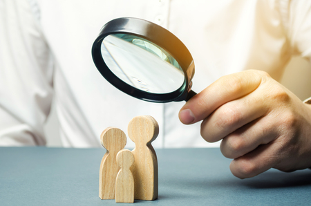 A person looks at family figures through a magnifying glass. The study of family composition, statistics. Birth control and juvenile police. The study of society and the behavior. Marketing.