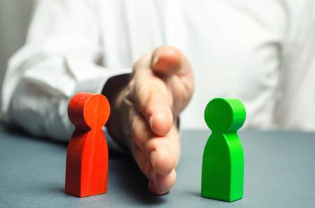La persona divide con la palma las figuras rojas y verdes de las personas. Orbiter, la solución de cuestiones controvertidas y conflictos de interés. Detén el conflicto, el mediador. Resolución de conflictos. Foto de archivo
