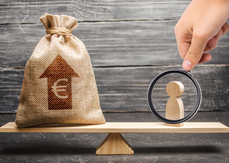 Magnifying glass is looking at a man figurine and Euro money bag with arrow up on scales. average salary in the labor market, pricing. Criteria and requirements for increasing the work of a specialist 免版税图像 - 117670587