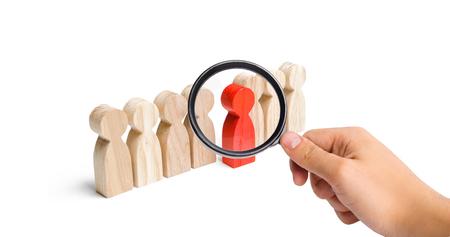 La lente d'ingrandimento sta guardando la figura rossa di un uomo che esce dalla fila delle persone. Talento, leader, professionista. successo e miglioramento nel lavoro, il riconoscimento universale dell'efficienza
