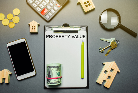 Table with wooden houses, calculator, coins, magnifying glass with the word Property value. The contract for real estate appraisal. Rate the property. Valuation house. Appraisal Services. Flat lay