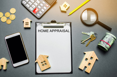 Table with wooden houses, calculator, coins, magnifying glass with the word Home appraisal. The contract for real estate appraisal. Rate the property. Valuation services. Value house. Flat lay