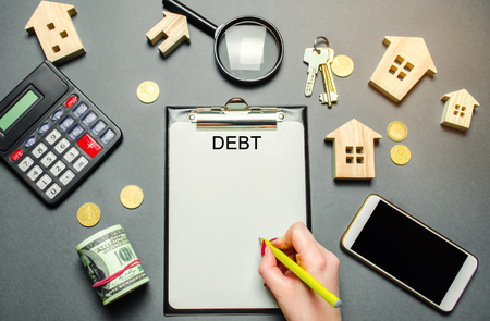 Table with wooden houses, calculator, coins, magnifying glass with the word Debt. The concept of debt for housing. Mortgage. Credit. Real estate, loans market concept. Debt repayment. Flat lay