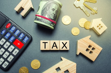 Wooden houses, a calculator, keys, coins and blocks with the word Tax. Property taxes. Calculation of interest on housing tax. Penalty, arrears. Register of taxpayers for property. Flat lay